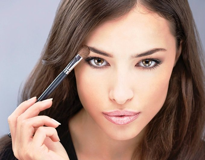 pretty-black-hair-woman-applying-make-up-with-brush-in-her-right-hand